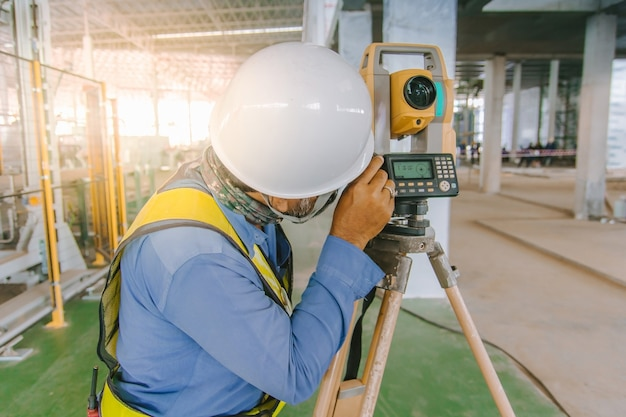 Ouvrier ingénieur géomètre effectuant des mesures avec un équipement au théodolite sur un chantier de construction.