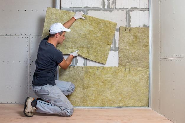 Ouvrier isolant un mur de pièce avec une isolation thermique en laine de roche minérale