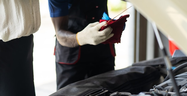 Ouvrier mécanicien automobile vérifiant le niveau d'huile dans le moteur de la voiture. concept de garage d'entretien automobile et de service automobile.
