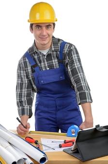 Un ouvrier mesure une planche avec un ruban à mesurer