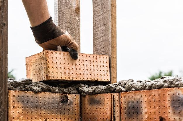 Un ouvrier met des briques sur le mortier