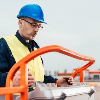 Ouvrier opérant un élévateur à flèche droite