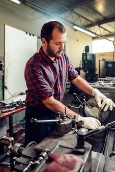 Ouvrier ouvrant une machine à tour dans l'usine industrielle