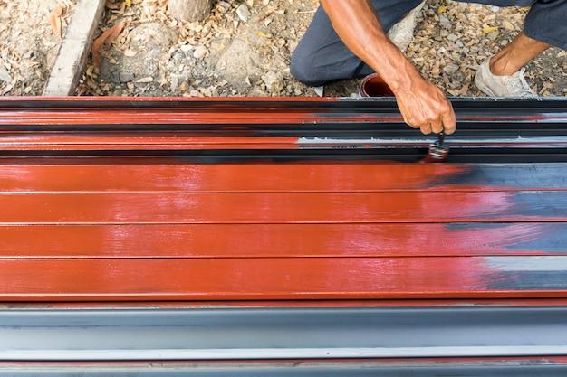 Un ouvrier peint antirouille sur des poteaux en acier pour la construction.