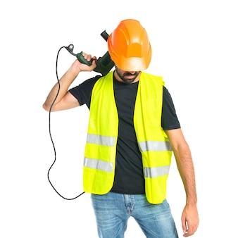 Ouvrier avec perceuse sur fond blanc