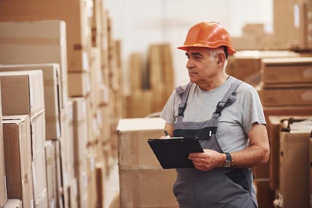 Un ouvrier principal du stockage en uniforme et un bloc-notes en mains vérifie la production.