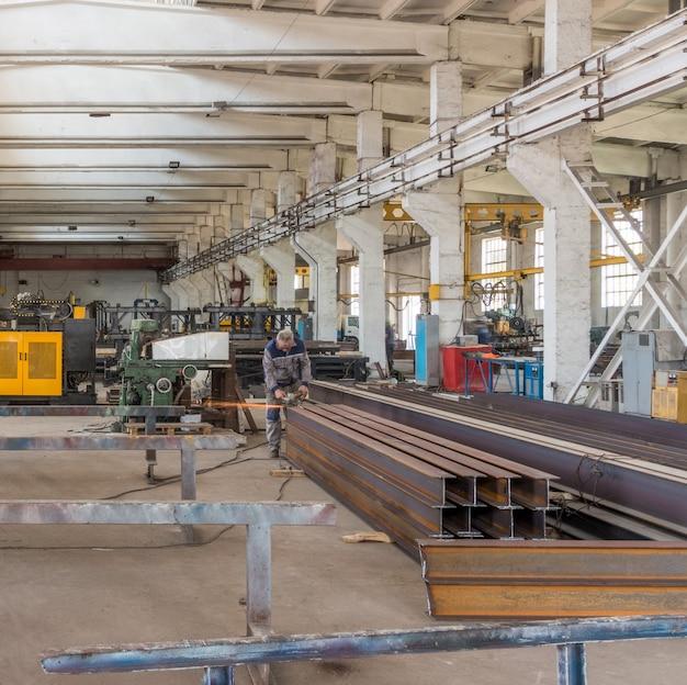 Un ouvrier produit en travaillant avec une meuleuse en métal. un ouvrier dans un atelier de métallurgie
