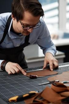Ouvrier qualifié de fabrication de cuir coupant quelques échantillons.