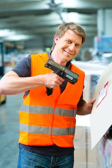 Un ouvrier scanne un colis dans un entrepôt d'expédition