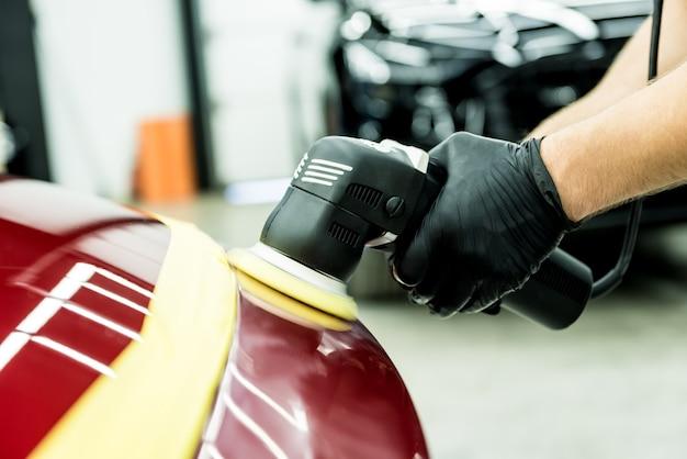 Un ouvrier de service de voiture polit les détails d'une voiture avec une polisseuse orbitale.