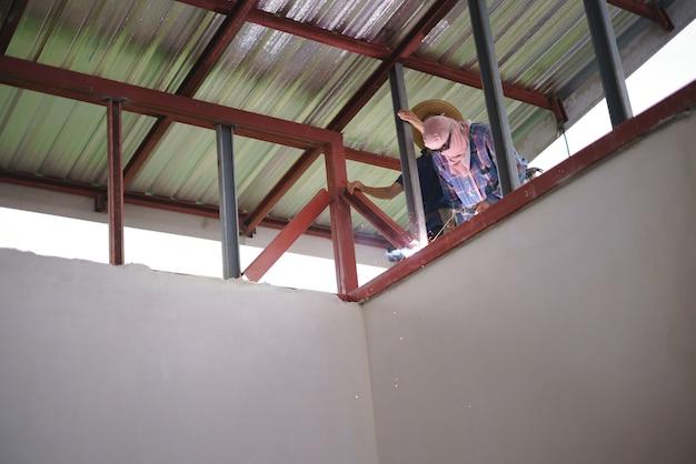 Ouvrier soudant du métal pour la construction du toit