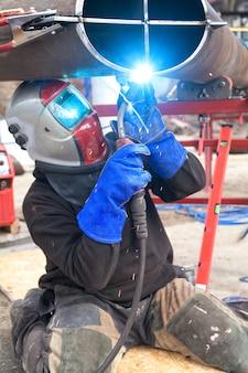 Ouvrier soudeur dans une usine. soudage sur une installation industrielle.