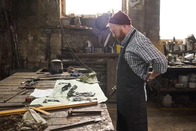 Ouvrier en tablier debout devant son lieu de travail avec des outils et commençant à travailler en atelier