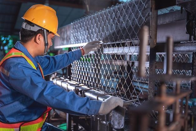 Ouvrier technicien asiatique contrôlant le treillis métallique