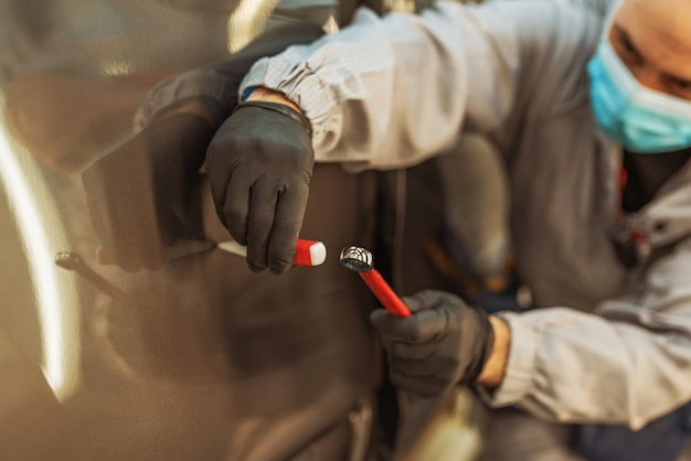 Un ouvrier d'usine automobile portant un masque médical de protection répare un petit défaut métallique avec un outil à main