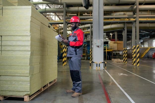 Ouvrier d'usine comptant des matériaux