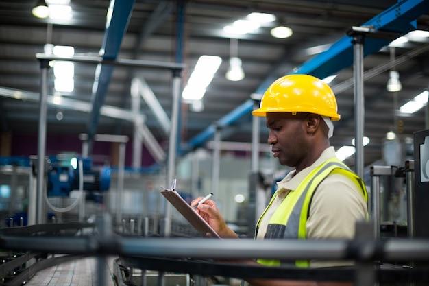 Ouvrier d'usine écrivant sur le presse-papiers