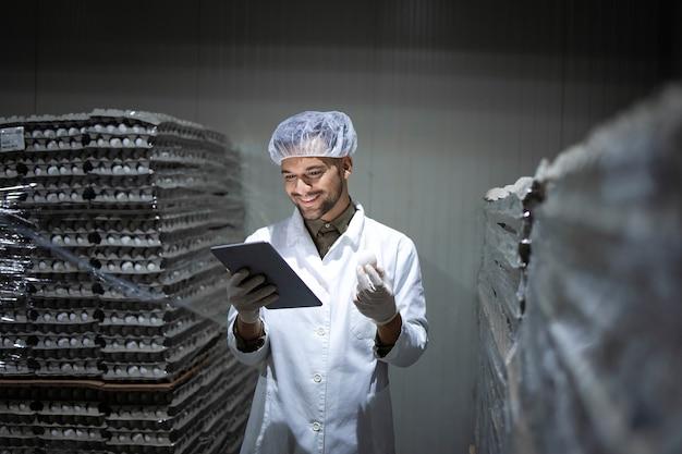 Ouvrier d'usine avec un filet à cheveux et des gants hygiéniques tenant un ordinateur tablette et vérifier l'inventaire dans la chambre froide des aliments.