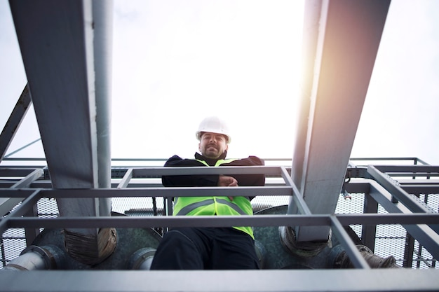 Ouvrier d'usine industrielle s'appuyant sur la balustrade de construction métallique de l'usine de production au coucher du soleil.
