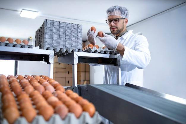 Ouvrier d'usine tenant des œufs et debout par une machine d'emballage dans une ferme alimentaire.