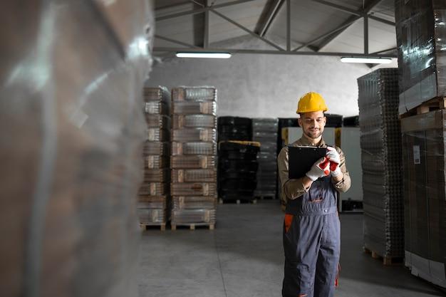 Ouvrier d'usine en uniforme de protection et casque de sécurité expédiant les marchandises de l'entrepôt au marché.