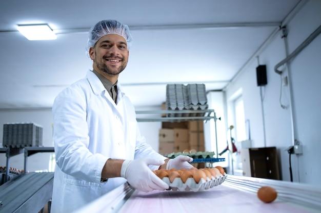 Ouvrier d'usine en vêtements stériles, résille à cheveux et gants hygiéniques travaillant à l'emballage des œufs industriels dans une usine de transformation des aliments.
