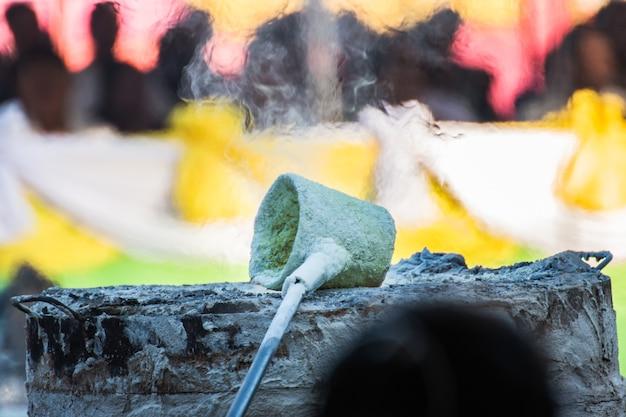 Ouvrier versant du métal en fusion pour couler la statue de bouddha.