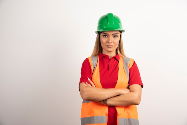 Ouvrière industrielle féminine posant en uniforme et casque.