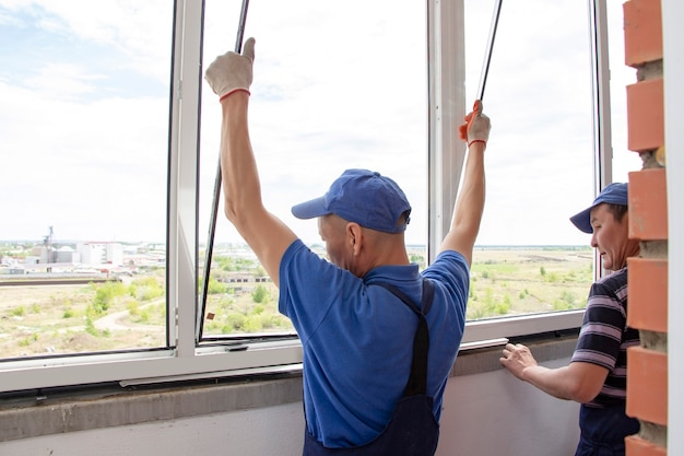 Les ouvriers artisans installent une fenêtre dans la maison