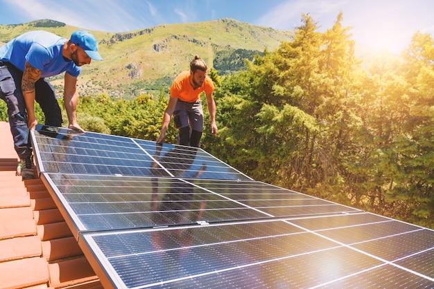 Les ouvriers assemblent le système énergétique avec le panneau solaire pour l'électricité et l'eau chaude