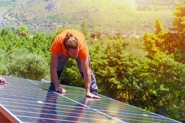 Les ouvriers assemblent le système énergétique avec le panneau solaire pour l'électricité