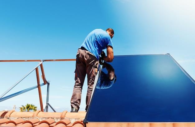Les ouvriers assemblent le système d'énergie avec l'eau chaude de panneau solaire