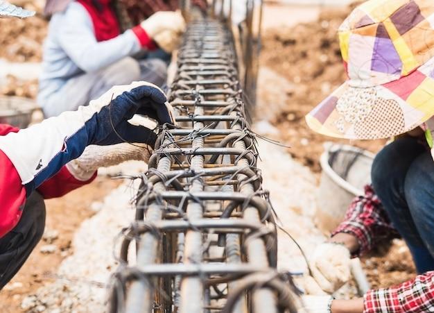 Les ouvriers du bâtiment installent des tiges d'acier dans une poutre en béton armé
