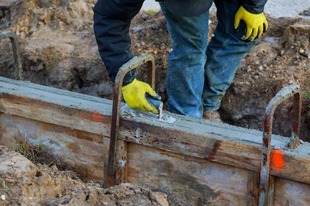 Ouvriers du bâtiment nivelant la chaussée en béton.