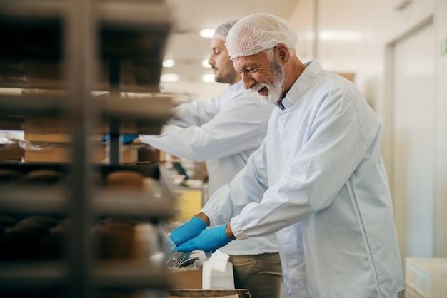 Ouvriers emballant des biscuits dans des boîtes en se tenant debout dans une usine alimentaire.