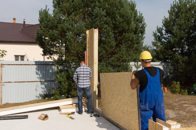 Ouvriers érigeant des panneaux isolants muraux revêtus de planches de bois alors qu'ils travaillent sur un nouveau chantier de construction de maisons