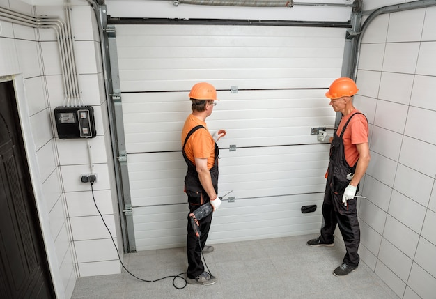 Les ouvriers installent des barrières d'ascenseur dans le garage.