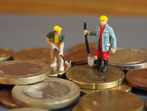 Des ouvriers miniatures se tiennent sur des pièces en euros. concept d'entreprise et d'idée.