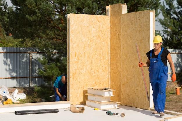 Ouvriers occupés à ériger des murs isolés sur un chantier de construction installant les unités d'angle sur le sol nouvellement posé