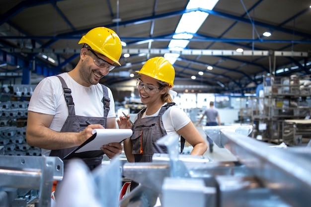 Les ouvriers de l'usine analysent les résultats de production dans un grand hall industriel