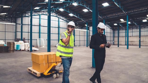 Les ouvriers de l'usine livrent des boîtes sur un chariot poussant dans l'entrepôt.
