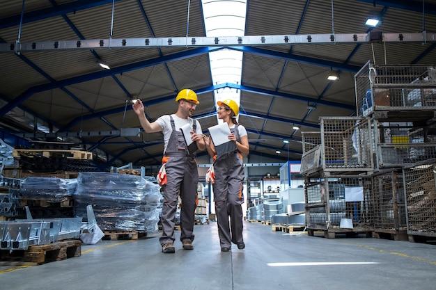Ouvriers de l'usine marchant dans un grand hall de production et ayant une conversation