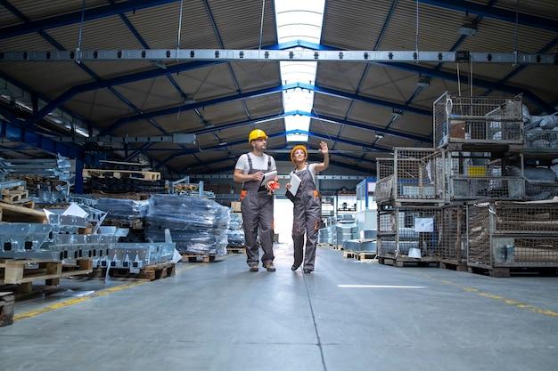 Ouvriers d'usine marchant dans un grand hall de production
