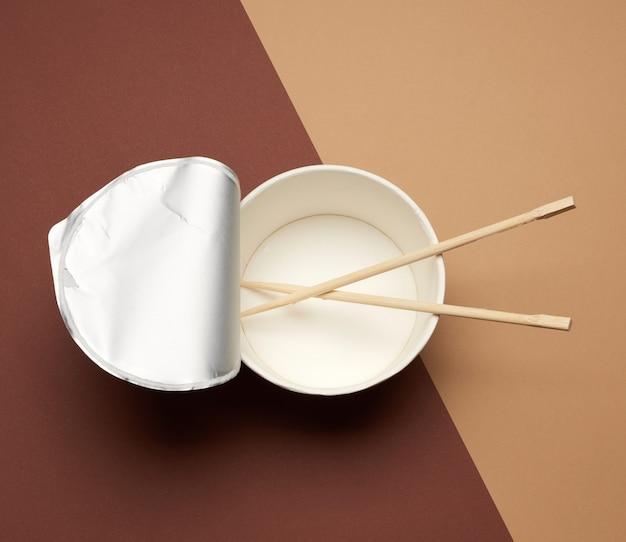 Ouvrir le bol de nouilles vide avec couvercle en aluminium et paire de bâtonnets en bois