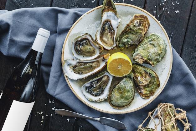 Ouvrir les huîtres humides sur une assiette avec du citron