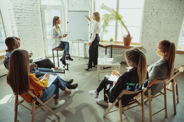 Ouvrir les informations. conférencière faisant une présentation dans le hall de l'atelier. centre d'affaires. vue arrière des participants en public. conférence événement, formation. éducation, diversité, concept inclusif.