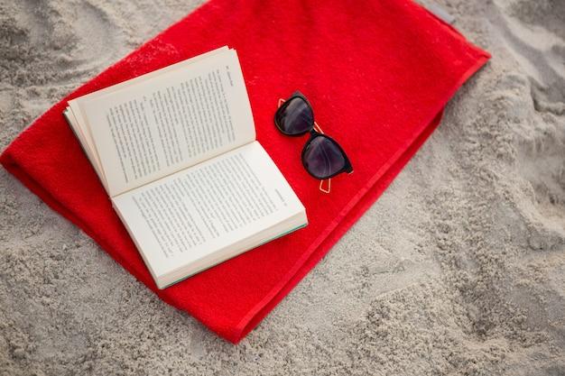 Ouvrir le livre et des lunettes de soleil conservés sur la serviette rouge