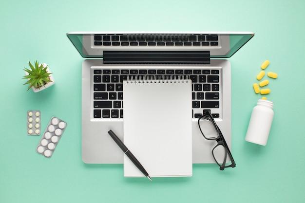Ouvrir un ordinateur portable avec des pilules et un journal sur une surface verte