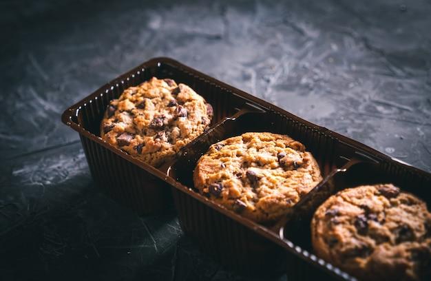Ouvrir le paquet de cookies aux pépites de chocolat sur une table sombre