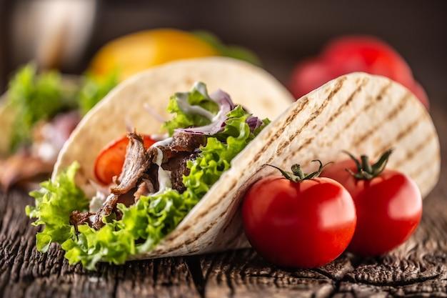 Ouvrir la tortilla de viande et de légumes sur une planche de bois rustique.
